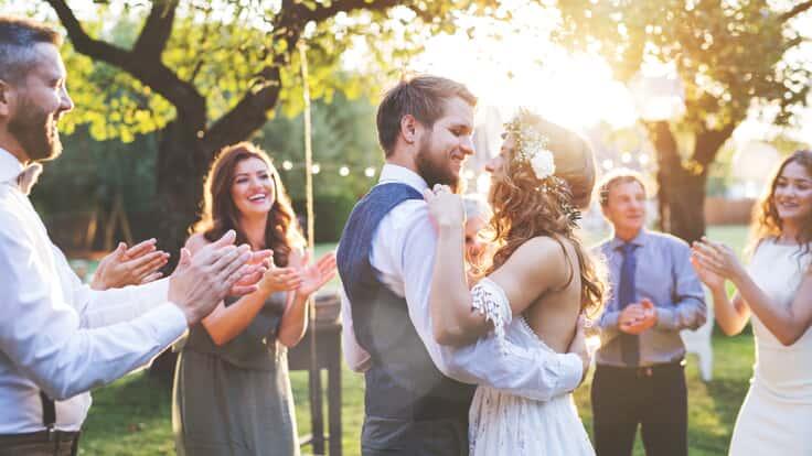 Hochzeitspaar tanzt und feiert mit Freunden im Freien