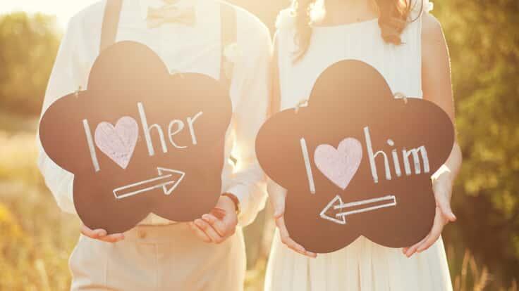 Hochzeitspaar mit Schildern in der Hand - I love her - I love him. Wir als Hochzeit DJ lieben gute Musik